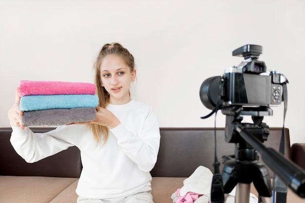 Tiro médio menina dobrar toalhas em casa
