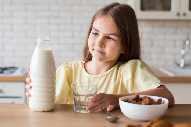 Tiro médio, menina, segurando, garrafa leite