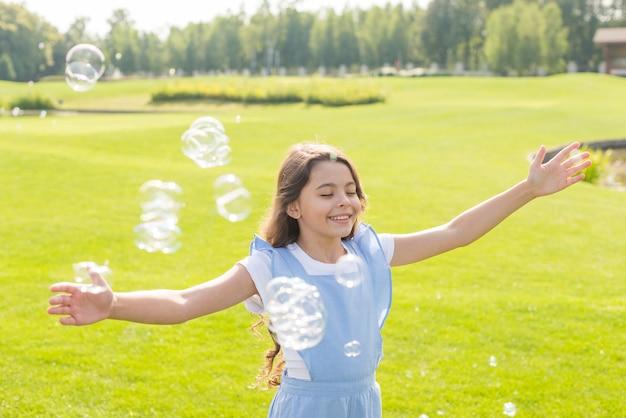 Tiro médio, menina, tocando, com, bolhas sabão, ao ar livre