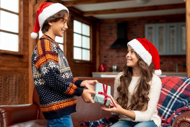 Tiro médio menino e menina com presente olhando uns aos outros