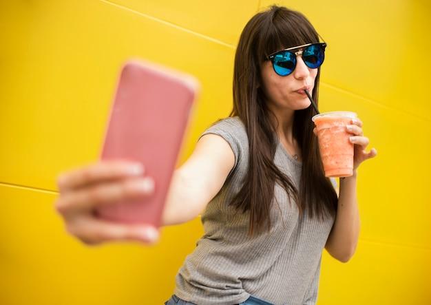 Tiro médio mulher bebendo suco e tomando uma selfie