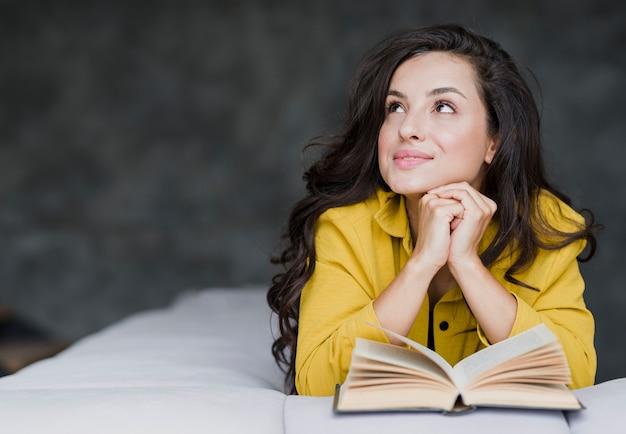 Tiro médio mulher com livro olhando para longe