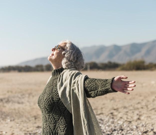 Tiro médio mulher com óculos de sol ao ar livre