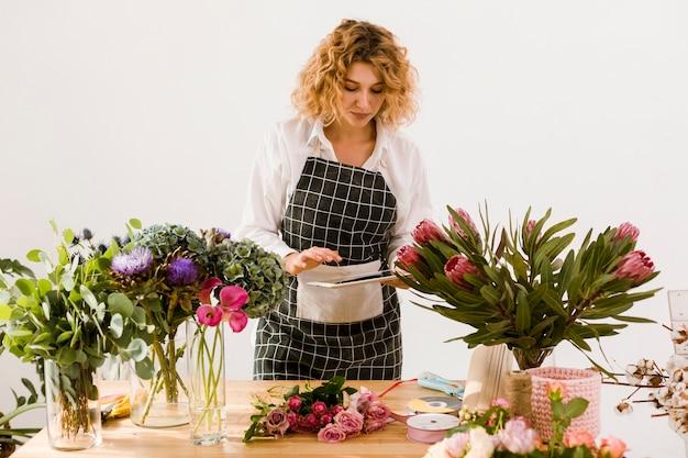 Tiro médio mulher com tablet na loja de flores