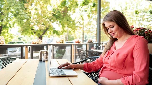 Tiro médio mulher grávida com laptop em um terraço