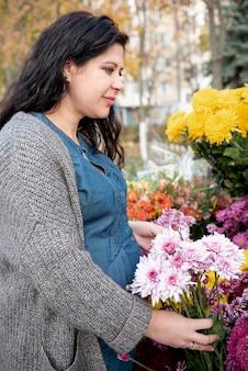 Tiro médio, mulher grávida, segurando, buquê flores