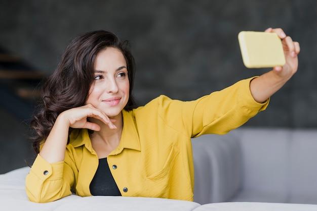 Tiro médio mulher morena tomando um telefone