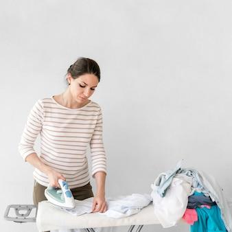 Tiro médio mulher passando roupa