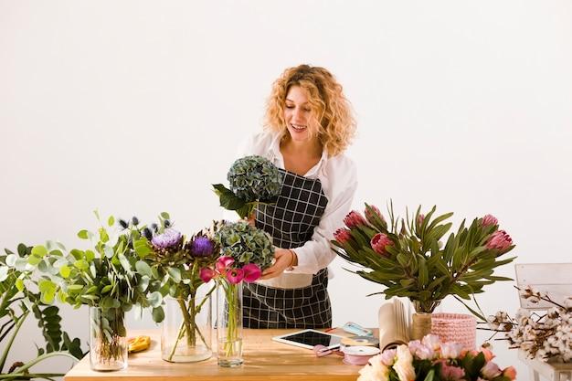 Tiro médio mulher que trabalha em uma loja de flores