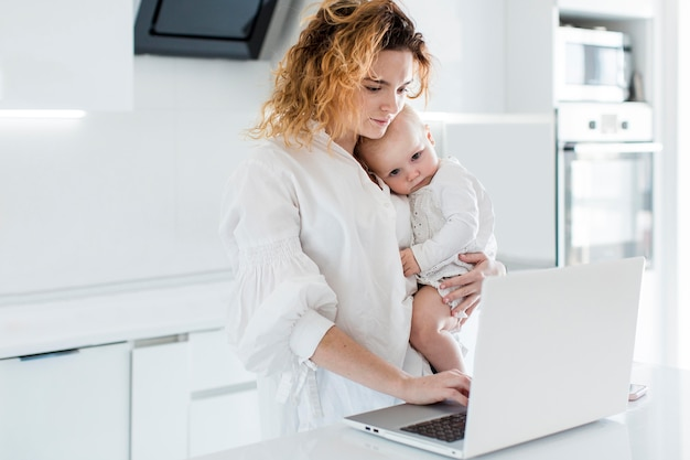 Tiro médio, mulher segura bebê