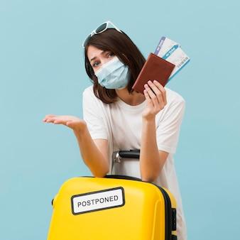 Tiro médio, mulher segura, bilhetes avião, e, bagagem amarela