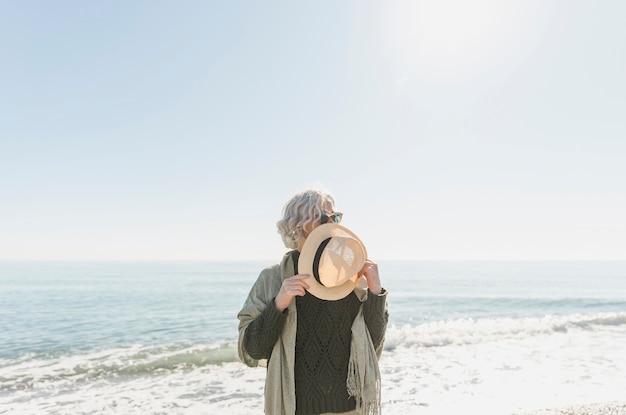Tiro médio, mulher segura, chapéu palha