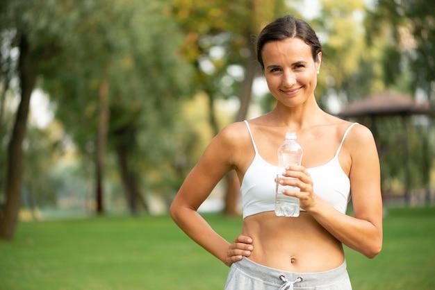 Tiro médio, mulher segura, garrafa água