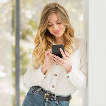 Tiro médio, mulher segura telefone