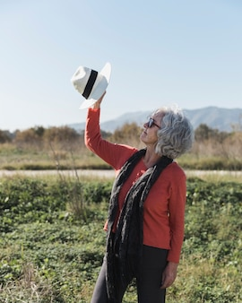 Tiro médio mulher segurando um chapéu