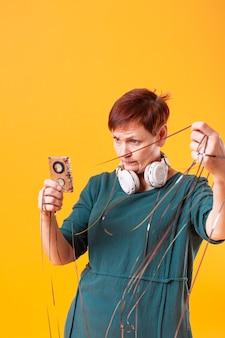 Tiro médio, mulher sênior, tocando, com, fita cassete