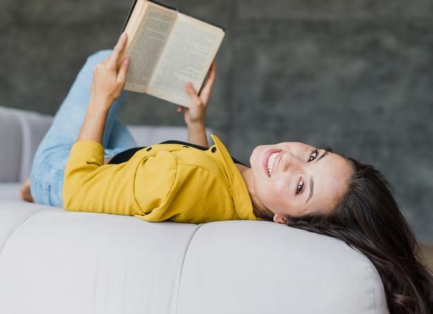 Tiro médio mulher sentada nas costas com o livro