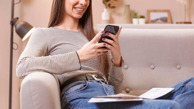Tiro médio mulher sentada no sofá e trabalha