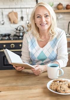 Tiro médio mulher sorridente com livro na cozinha