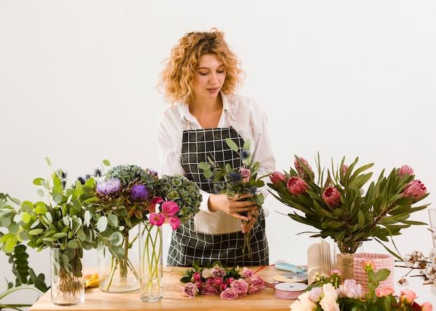 Tiro médio mulher trabalhando na loja de flores