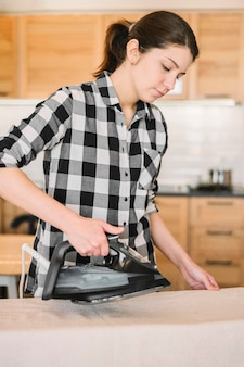 Tiro médio mulher usando ferro