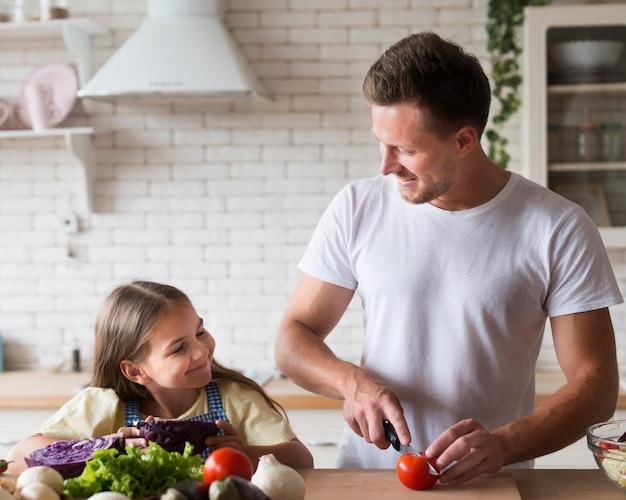 Tiro médio pai e filha cozinhar