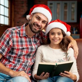 Tiro médio pai e filha posando com livro