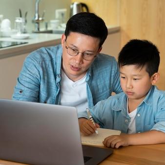 Tiro médio, pai e filho fazendo lição de casa