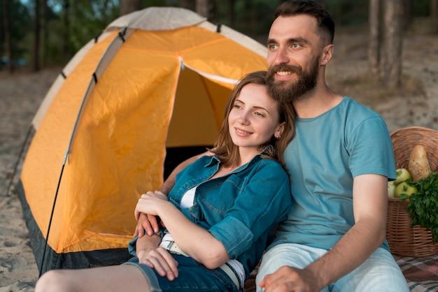 Tiro médio, par acampando, olhando,