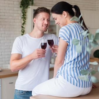Tiro médio, par, segurando, copos vinho