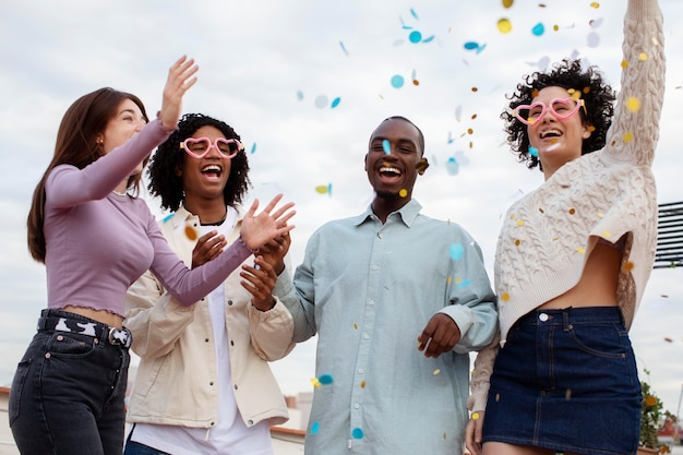Tiro médio pessoas felizes festejando com confete