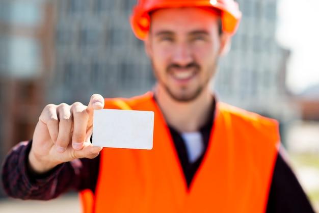 Tiro médio, retrato, de, engenheiro construção, segurando, cartão negócio