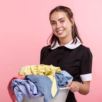 Tiro médio, smiley, empregada, com, lavanderia, bacia