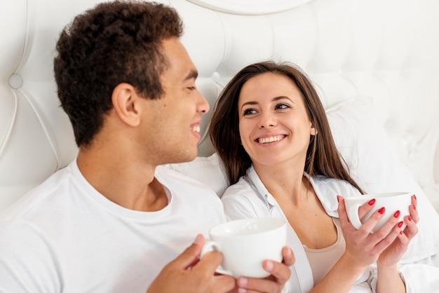 Tiro médio sorridente casal com copos de café