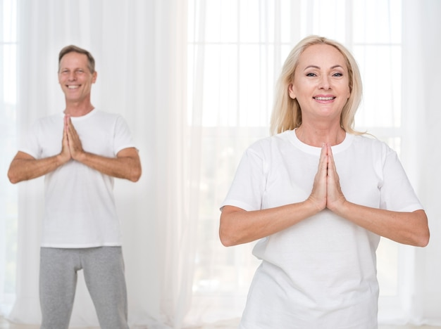 Tiro médio sorridente casal meditando juntos