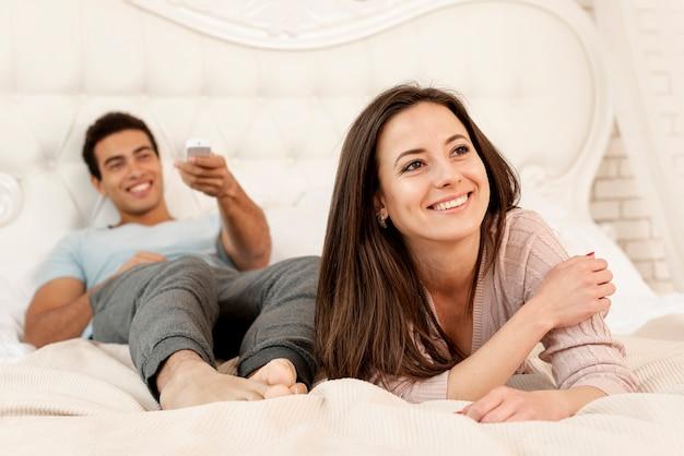 Tiro médio sorridente casal no quarto
