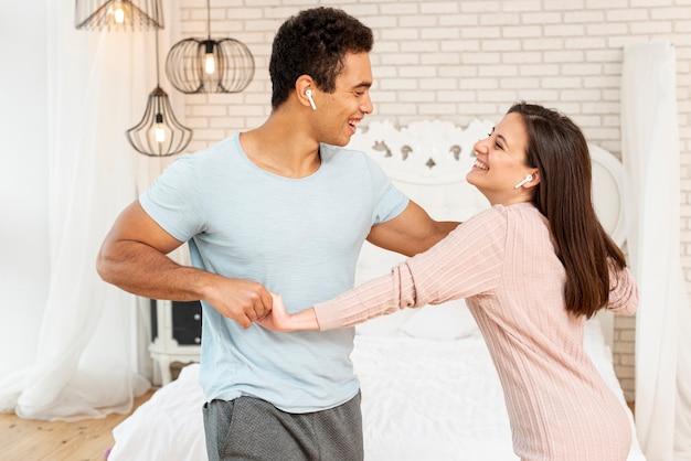 Tiro médio sorridente casal ouvindo música no quarto