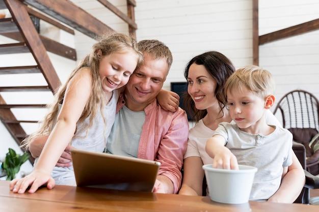 Tiro médio sorridente família olhando para tablet