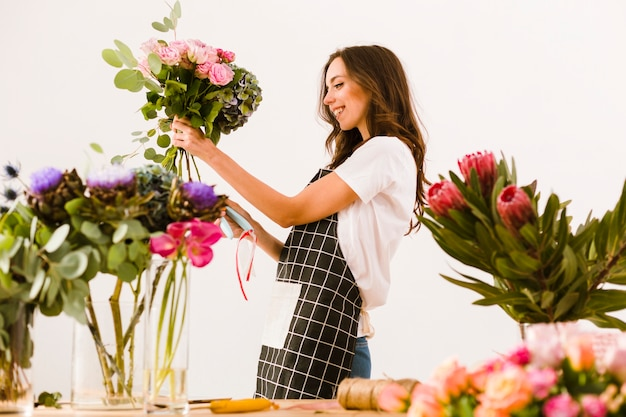 Tiro médio sorridente florista fazendo um buquê