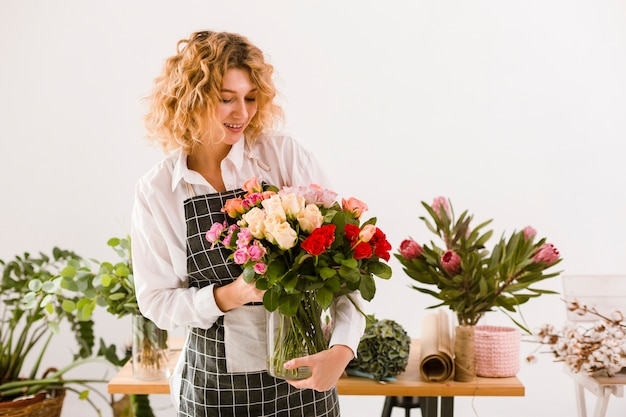 Tiro médio sorridente florista segurando o frasco com flores