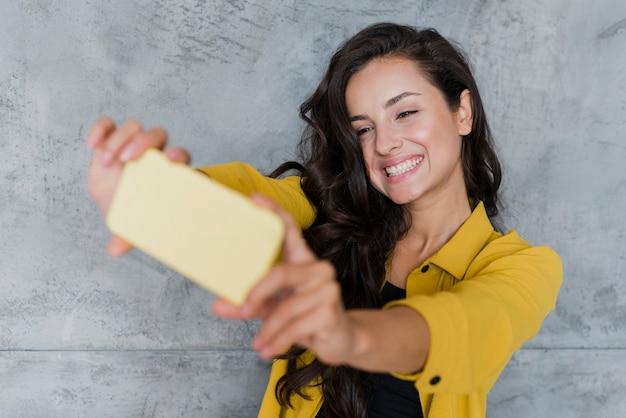 Tiro médio sorridente garota tomando uma selfie