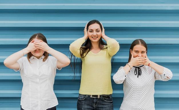 Tiro médio sorridente garotas cobrindo os olhos, ouvidos e boca