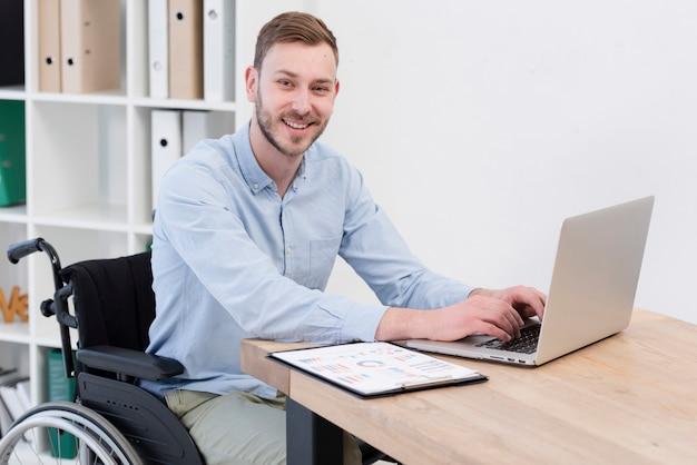 Tiro médio sorridente homem com laptop