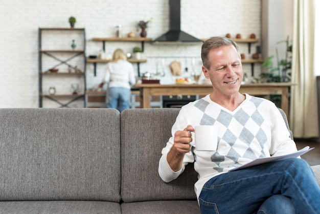 Tiro médio sorridente homem lendo no sofá