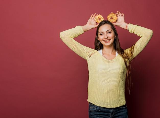 Tiro médio sorridente menina com donuts e cópia-espaço