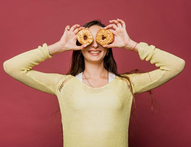 Tiro médio sorridente menina com donuts