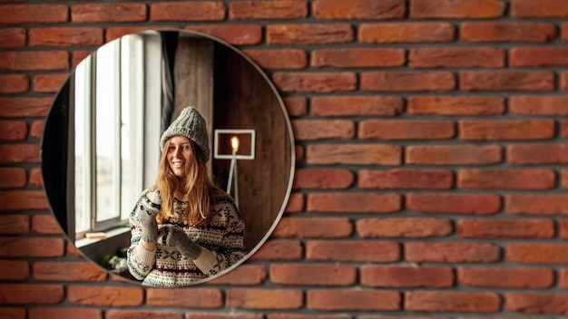 Tiro médio sorridente menina posando no espelho