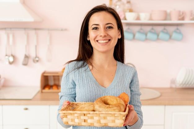 Tiro médio sorridente mulher com cesto de pastelaria
