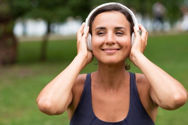 Tiro médio sorridente mulher com fones de ouvido