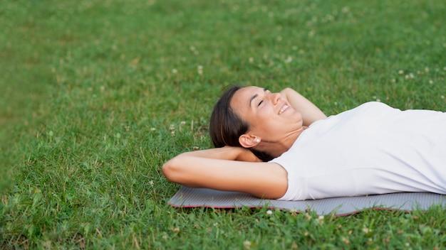 Tiro médio sorridente mulher deitada na grama